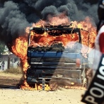 Armed Zambian police officers stand near a burning truck in Lusaka's Kanyama area during election riots Stone-throwing mobs smashed cars and blocked roads during voting, after opposition leader Michael Sata accused President Rupiah Banda's rival camp of rigging the ballot.